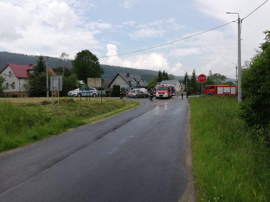 na zdjęciu widać pojazdy pokolizyjne, policjantów, strażaków pracujących na miejscu zdarzenia, jak również radiowóz i wóz strażacki
