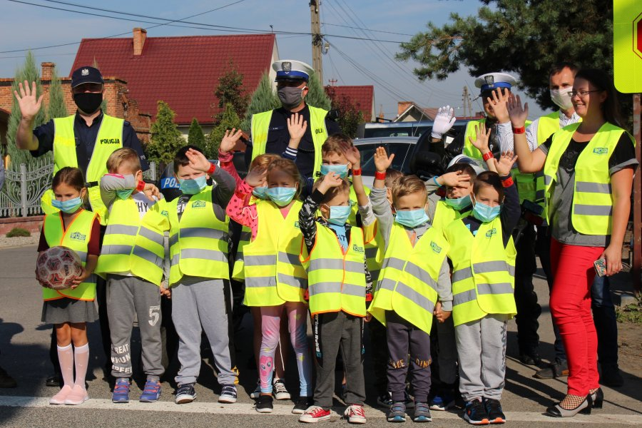 Policjanci podczas działań i uczniowie szkoły podstawowej w Trześni
