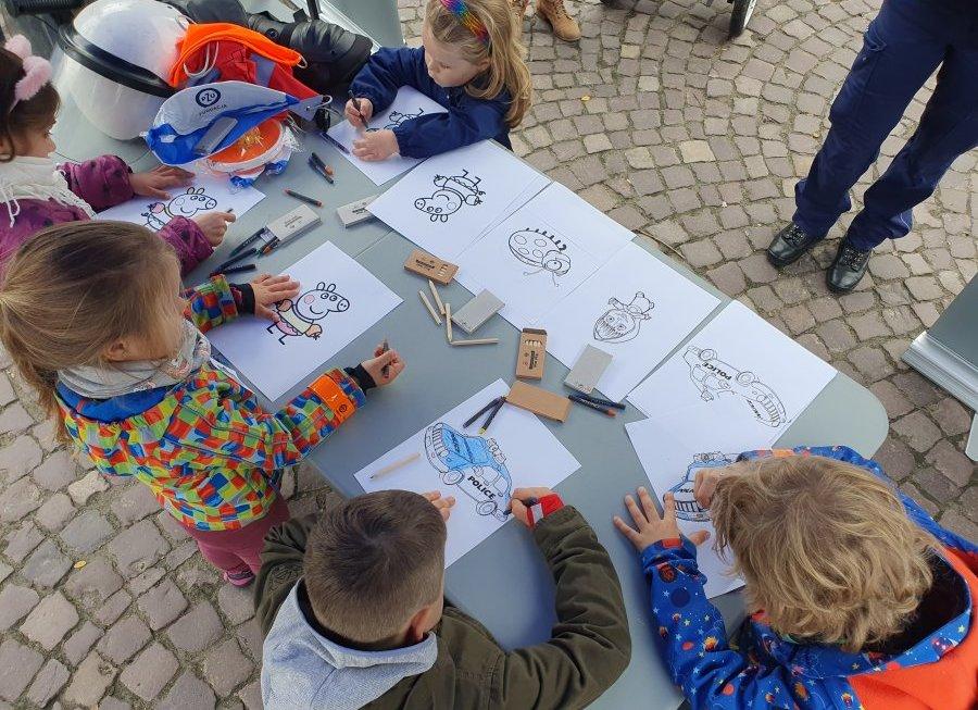 Na zdjęciu dzieci bawiące się przy policyjnym stoisku. Trzy dziewczynki i dwóch chłopców rysujących kolorowanki.