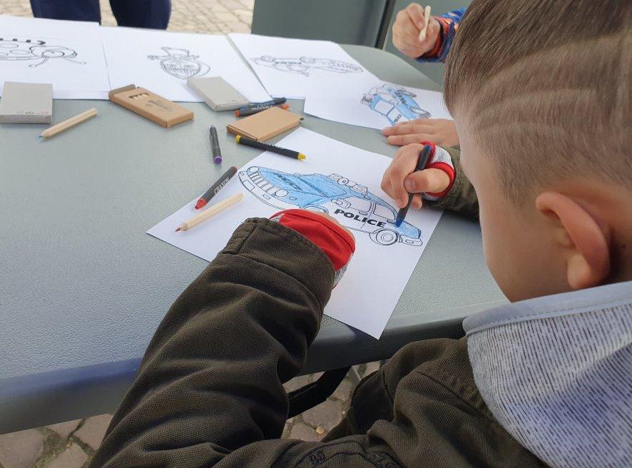 Na zdjęciu chłopiec kolorujący rysunek radiowozu.
