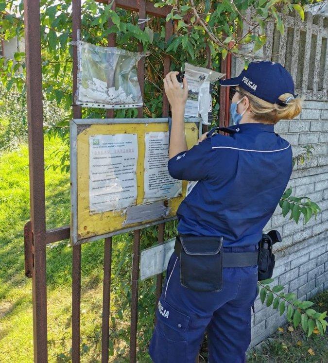 Policjantka zawieszająca ulotkę na tablicy ogłoszeń przed bramą orodów działkowych