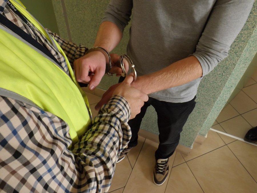 Policjant zakłada kajdanki zatrzymanemu.