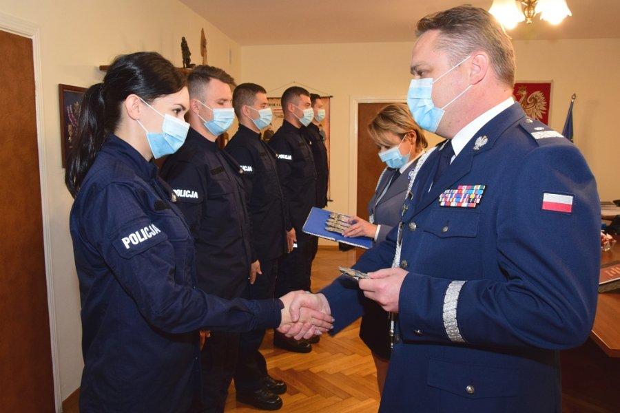 Policjantka odbiera legitymację służbową z rąk Komendanta Wojewódzkiego Policji w Rzeszowie nadinspektora Henryka Moskwy. Wszyscy uczestnicy uroczystości w maseczkach