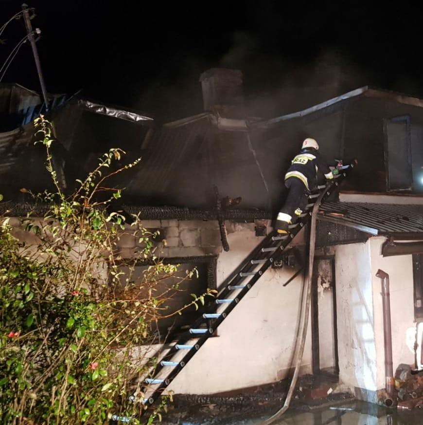 Na zdjęciu strażak na drabinie podczas gaszenia poddasza budynku.