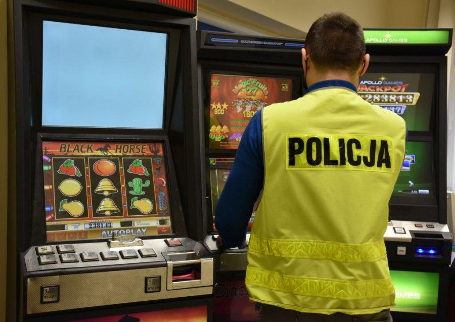 Trzy automaty do gier hazardowych. Przed nimi stoi policjant w kamizelce z napisem Policja
