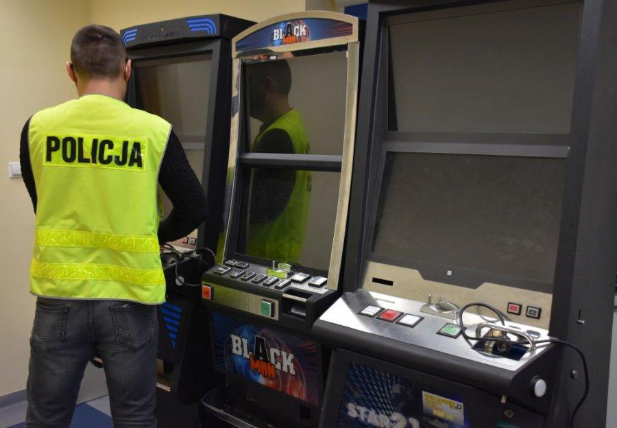 Zabezpieczone automaty do gier hazardowych. Przed nimi stoi mężczyzna w kamizelce odblaskowej z napisem Policja.