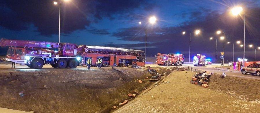 Wypadek autokaru na autostradzie A4. Pora nocna. Na pasie ruchu autostrady stoją wozy strażackie oraz strażacki dźwig. Na środku widać uszkodzony czerwony autokar i stojących obok policjantów. Na pierwszym planie rów, w którym widać leżące bagaże.