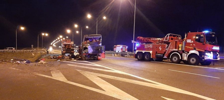 Wypadek autokaru w miejscowości Lutków na autostradzie A4. Pora nocna. Na środku widoczny uszkodzony autokar (widok od przodu), stojący na pasie ruchu autostrady. Po prawej stronie oraz z tyły w tle wozy strażackie. W tle policjanci i służby ratownicze.