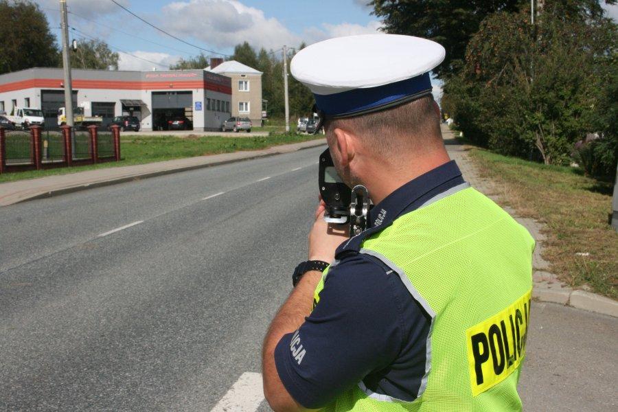 umundurowany policjant ruchu drogowego dokonuje pomiaru prędkości